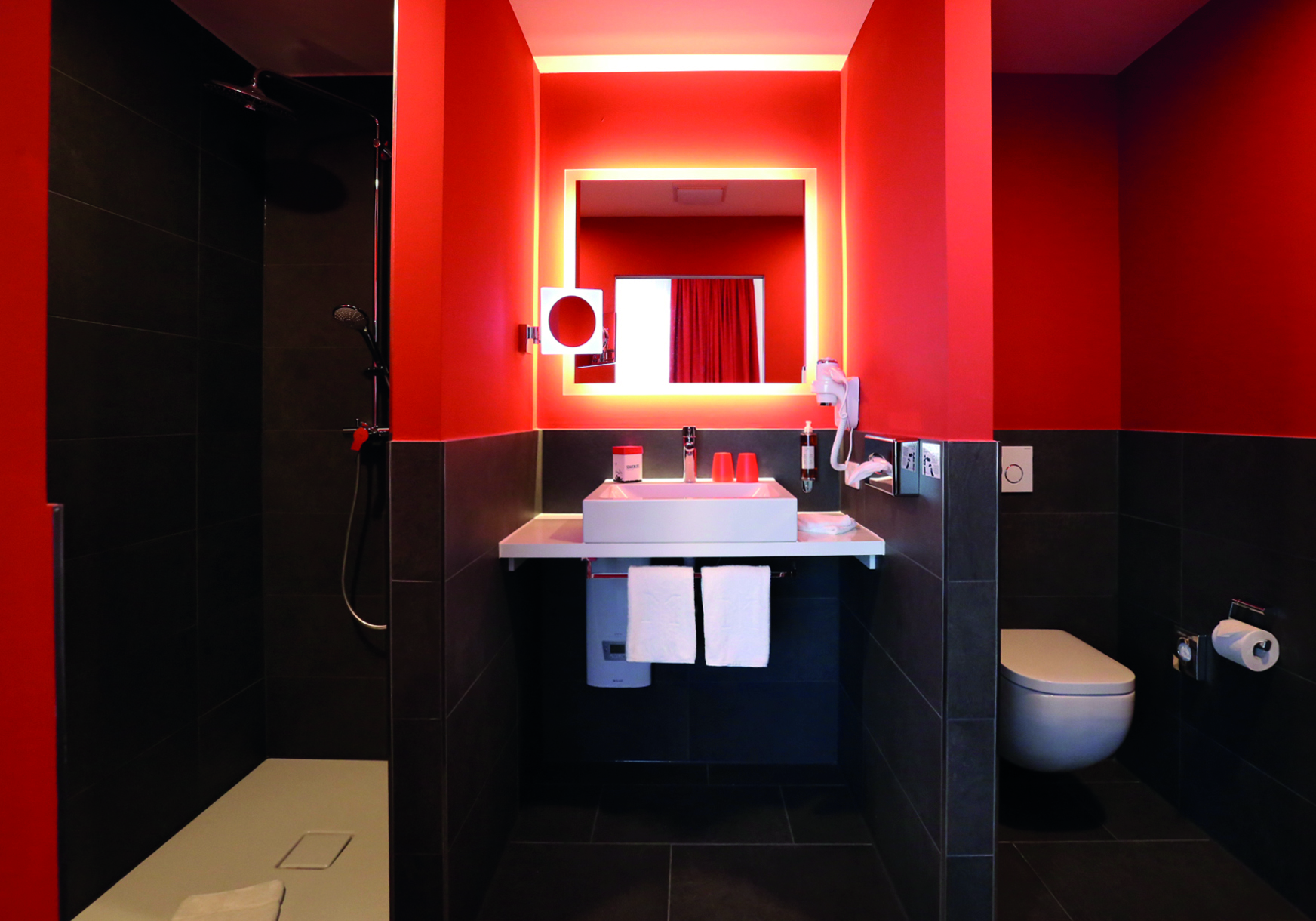 In the bathrooms of the Dormero Hotel in Roth, red walls and black tiles meet elegant washbasins and showers from the Kaldewei Cono series made from enamelled steel in alpine white. © Dormero Hotel AG